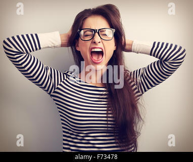 Angry young business woman in glasses strong screaming with wild open mouth and holding head the hands. Toned closeup - Stock Photo