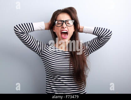 Anger young business woman in glasses strong screaming with wild open mouth and holding head the hands on blue background - Stock Photo