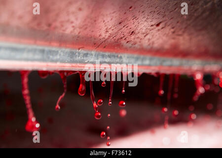 The interior of a grape press with droplets of fresh pressed juice dripping from a roller. - Stock Photo