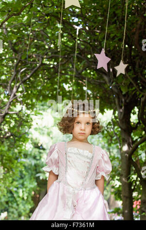 Young girl dressed as a fairy at a party in a garden. - Stock Photo