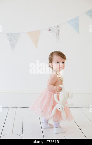 Young girl holding a cuddly toy, standing in a photographers studio, posing for a picture. - Stock Photo