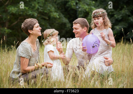 Family with two children playing in a meadow. - Stock Photo