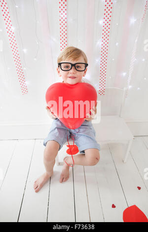 Young boy posing for a picture in a photographers studio, holding red balloons. - Stock Photo