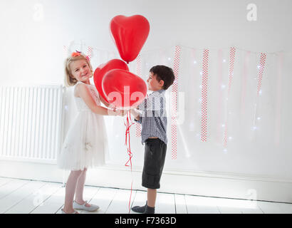 Young boy and girl posing for a picture in a photographers studio, holding red balloons. - Stock Photo