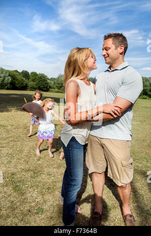 Couple standing in a park, smiling and embracing, children playing in the background. - Stock Photo