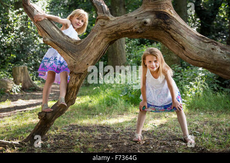 Two young girls climbing a tree in a forest. - Stock Photo
