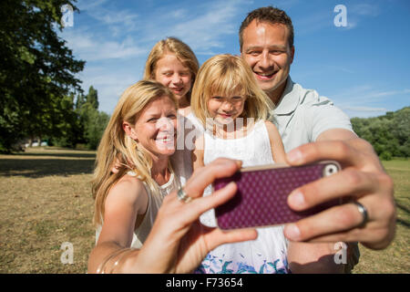 Family with two children, taking a selfie. - Stock Photo