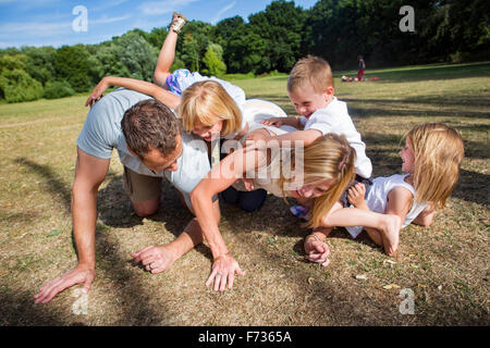 Family with three children playing in a park. - Stock Photo
