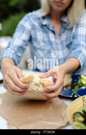 Woman tearing off a piece from a loaf of white bread. - Stock Photo