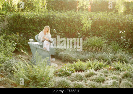 Blond woman sitting in a wicker chair in a garden, reading. - Stock Photo