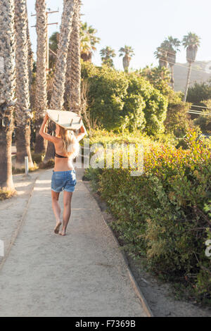 Blond woman in a black bikini and denim shorts carrying a surfboard on a path lined with palm trees. - Stock Photo