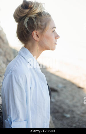 Profile portrait of a blond woman with a hair bun. - Stock Photo