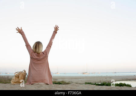 Blond woman sitting on a sandy beach, arms raised. - Stock Photo