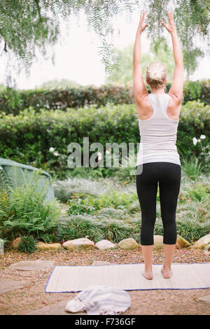Blond woman doing yoga in a garden. - Stock Photo
