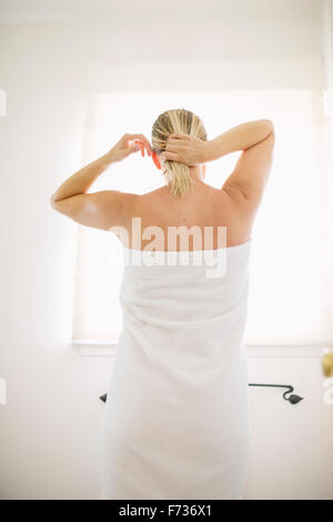 Woman wrapped in a white towel standing in a bathroom, tying her wet hair. - Stock Photo