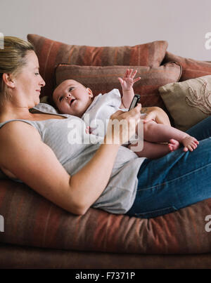 A woman lying on a sofa holding a baby girl, and holding a smart phone in one hand. - Stock Photo
