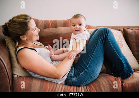 A woman lying on a sofa playing with a baby girl. - Stock Photo