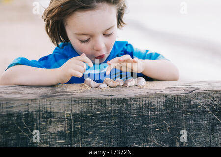 A boy at the beach counting shells lined up on a breakwater. - Stock Photo