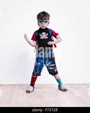 A boy standing with his legs apart posing in fancy dress, wearing a pirate tee-shirt, eye goggles and long shorts. - Stock Photo