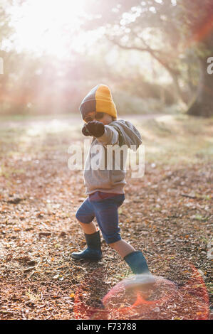 A boy outdoors in a woolly hat wearing shorts and wellington boots, striking a pose with an outstretched arm. - Stock Photo