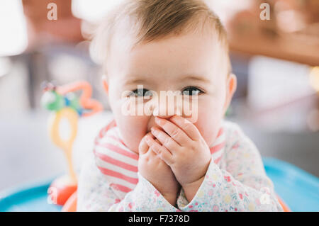 A baby girl with her hands covering her mouth, looking at the camera. - Stock Photo