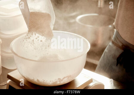 A baker preparing ingredients, using a measuring scale and pouring flour into a bowl. - Stock Photo