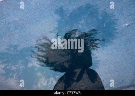 Double exposure of a young man twirling and tossing his hair with silhouette of a tree behind jute fabric - Stock Photo