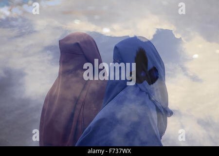 Double exposure of Muslim women wearing full Niqab veil and a bird flying in the sky - Stock Photo