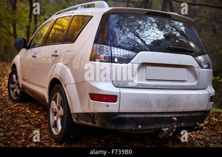 SUV car parked on a forest road covered in fallen leaves - Stock Photo