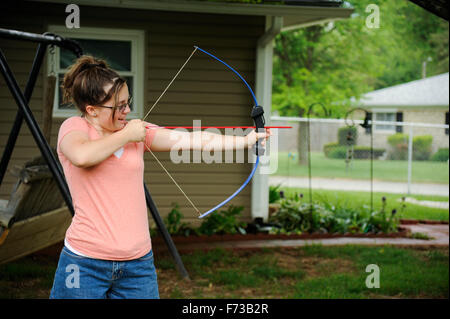 Pre-teen girl with bow and arrow in back yard - Stock Photo