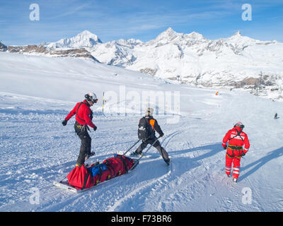 A rescue team is transporting a wounded skier on a rescue sled down the ski slope of ski resort Zermatt in the Swiss - Stock Photo