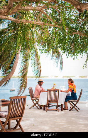 LAMU, KENYA, AFRICA. A man and woman sit under shade trees at a table on a patio overlooking blue water. - Stock Photo