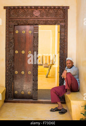 LAMU, KENYA, AFRICA. A man in traditional Arab dress sits on a becnh outside an antique carved-wood door. - Stock Photo