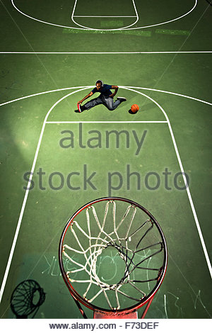 A basketball player stretches before a game. - Stock Photo