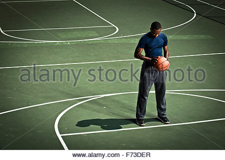 A basketball player practices free throws. - Stock Photo