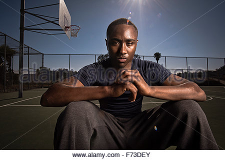 A basketball player rests on the court after a game. - Stock Photo
