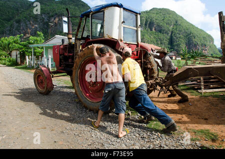 Three men push start a tracker in Viñales, Cuba. - Stock Photo