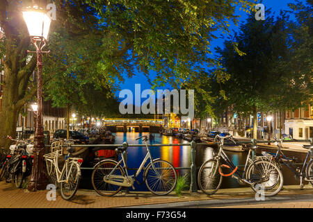 Night city view of Amsterdam canal and bridge - Stock Photo