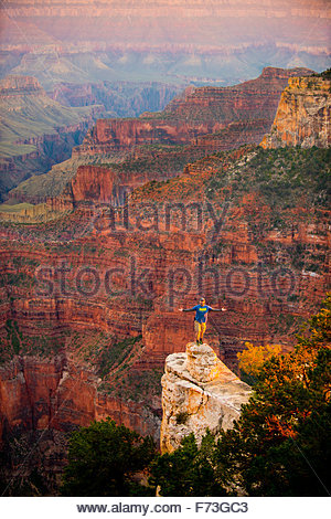 Man Standing on the Edge of the North Rim of the Grand Canyon with arms spread expressing the immensity of nature - Stock Photo