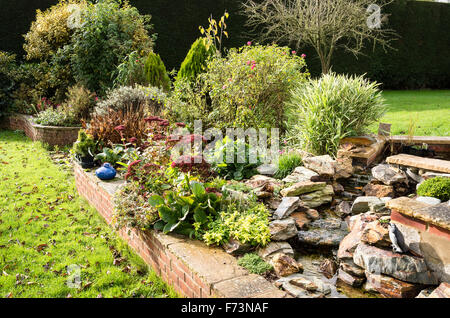 Waterfall and garden mixed herbaceous raised border in the Autumn - Stock Photo