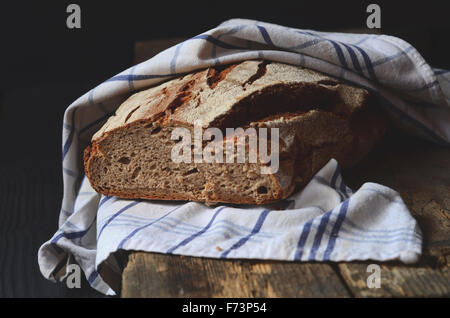 Freshly baked traditional homemade bread on wooden table - Stock Photo