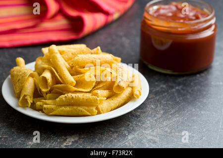 rolled nacho chips and salsa dip on kitchen table - Stock Photo