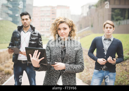 Multiracial business people posing outdoor in town holding technological devices like tablet, smartphone and computer - Stock Photo