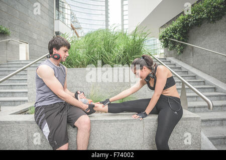 Couple of young hansome caucasian sportive man and woman helping each other stretching - he helps her to stretch - Stock Photo