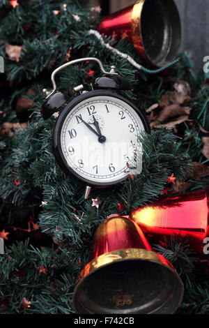 Christmas: Vintage alarm clock with hand bells on a New Year tree. - Stock Photo