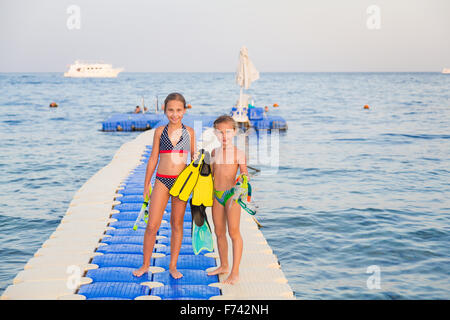 Cute girls with water masks and swim fins walking on pontoon - Stock Photo