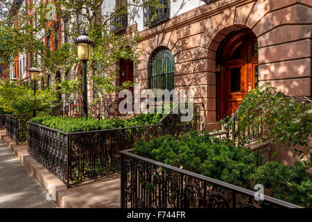 Row of townhouses and their lovely front yards and lampposts. Afternoon light in Chelsea, Manhattan, New York City. - Stock Photo