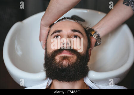 Hairstylist washing head of young attractive man with beard in barbershop - Stock Photo