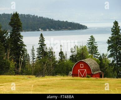 A red barn paints an idyllic scene in front of Flathead Lake, Montana, USA. - Stock Photo