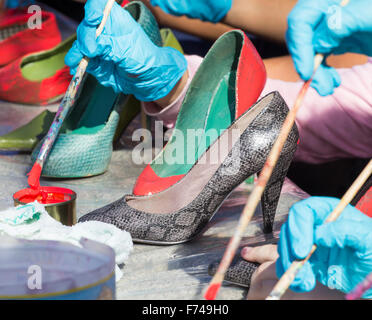 Las Palmas, Gran Canaria, Canary Islands, Spain. 25th November, 2015. Spanish schoolchildren paint shoes red at - Stock Photo